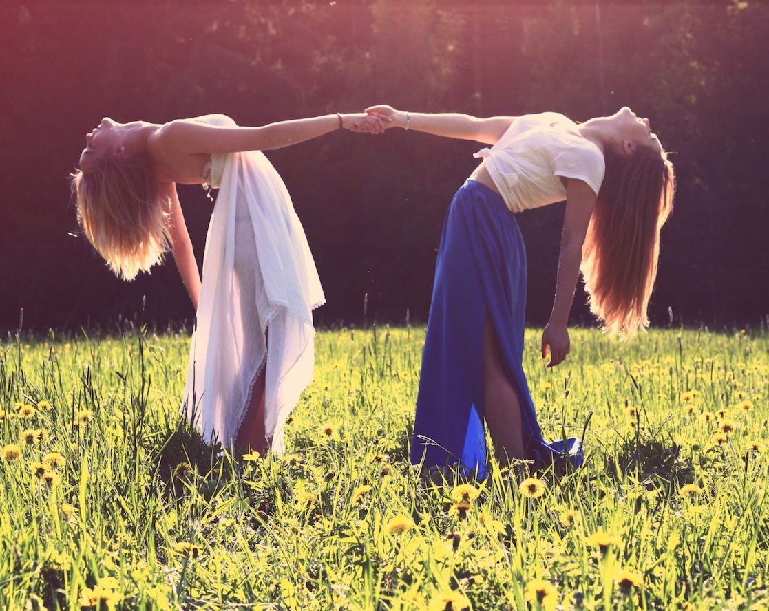 Two girls holding hands on the grass during daytime. Brooklyn Dance Lessons wedding package.