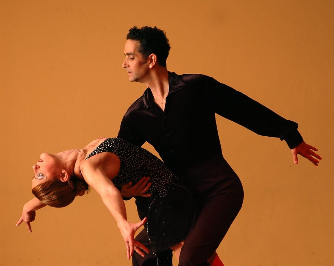 Professional couple dancing while wearing a black outfit. Brooklyn Dance Lessons wedding package.